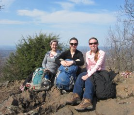 OEB students (from left) Emily Fusco, Laura Doubleday, and Hannah Broadley pose for a photo during a discussion of Sewall Wright's contributions to evolutionary biology atop Mt. Norwottuck in Mt. Holyoke Range State Park.